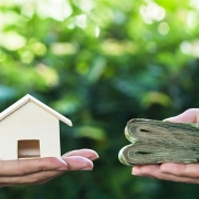 image of home and money held in hands
