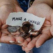 image of person holding coins and make a change sign